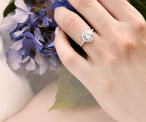 Stunning halo moissanite engagement ring holding hydrangeas